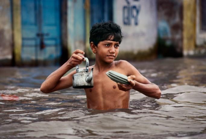 INDIA. Porbandar. 1983. Tea Vendor carries tea kettle in waist deep monsoon water.
